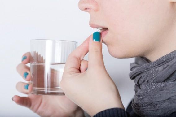 薬を飲む女性